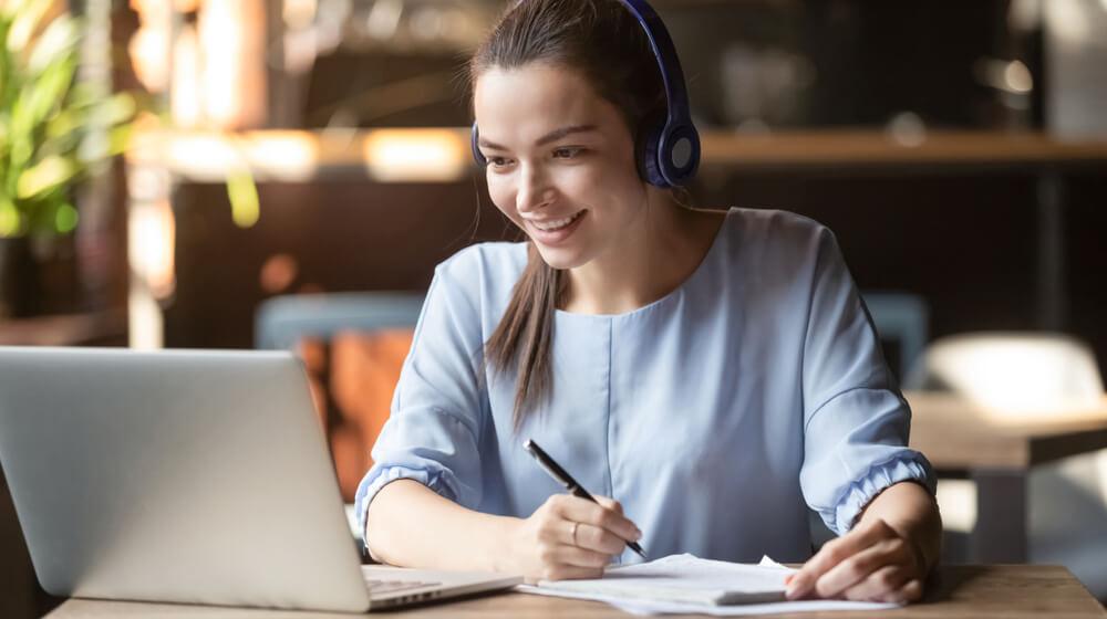 Smiling Girl Student Wear Wireless Headphone Study Online With Skype Teacher