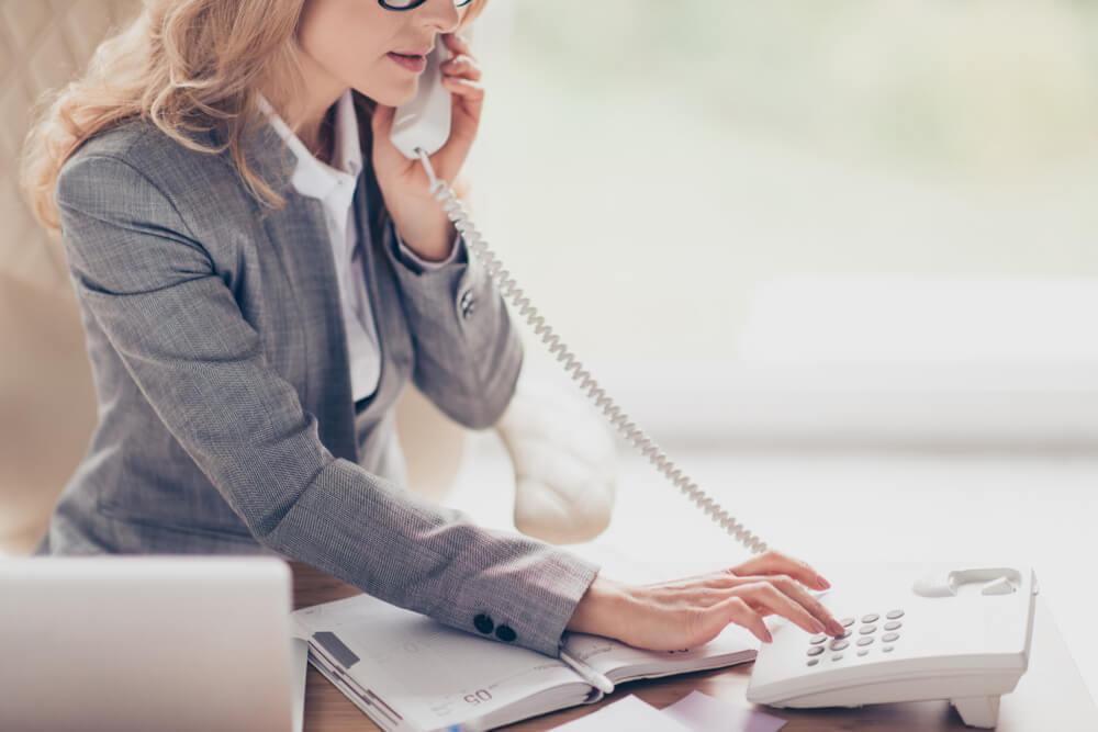 Professional Operator Wearing Formal Grey Suit Using a Landline Phone
