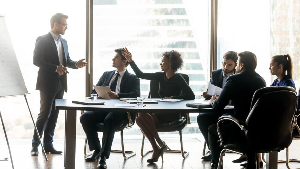 Empresaria afroamericana levantando la mano, preguntando al mentor del entrenador orador en la reunión corporativa